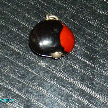 bean type charm with silver pin through it
