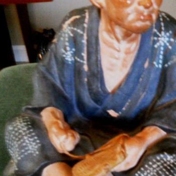 Ceramic Oriental man making shoes?