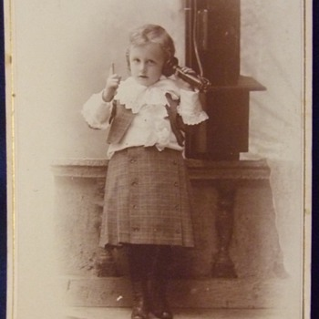 Cabinet card of toddler on wall mounted telephone
