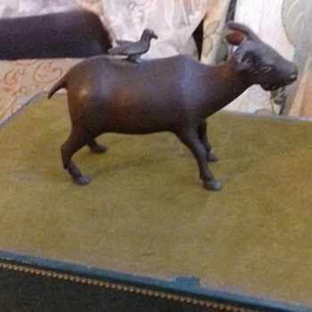 AN OLD BRONZE FIGURINE OF A GOAT WITH A BIRD SITTING ON TOP OF GOAT
