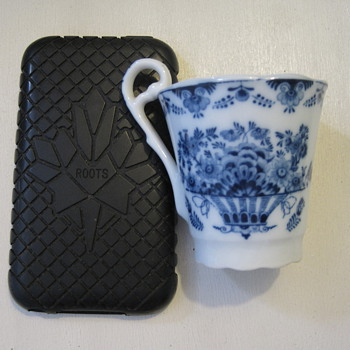 Diminutive blue and white cup with distinctive handle