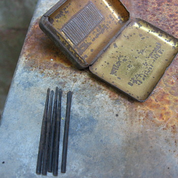 tiny screw driver heads and metal box, used for...?