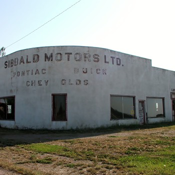 Old deserted Car Dealership . I love the shape of it .