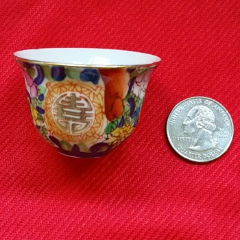 "Porcelain tea cups with gold rims and symbols. 1 1/2 "" tall"