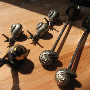 Silver snails, seperately and on a spoon and fork. 
