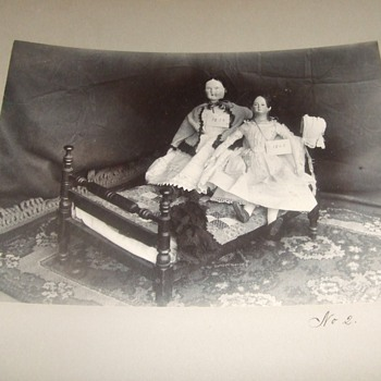Dolls displayed on doll sized rope bed