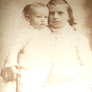 Cabinet card of two children with one holding a hammer - Photographs