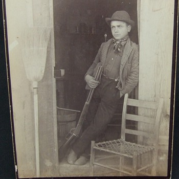 Cabinet card of youngster with a Winchester