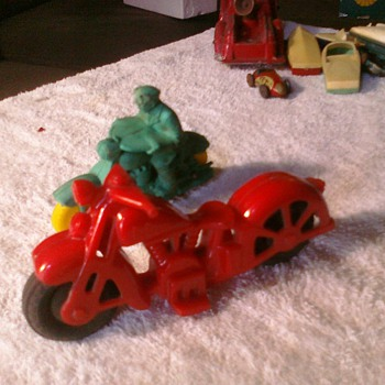 Old toy motorcycles.  The red is a hard plastic Harley or Indian and the other is most likely an Auburn Rubber toy