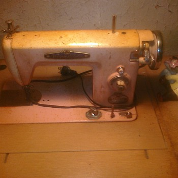 it says Voguestitches pink sewing machine in wooden cabinet