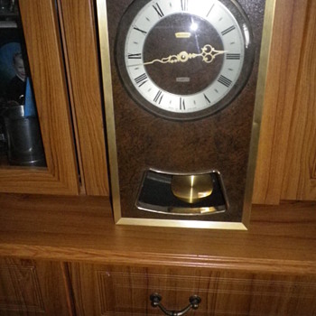 Metamec pendleum clock a 1980s quartz wall clock with brass, glass and a leather effect body all working and quite attractive.