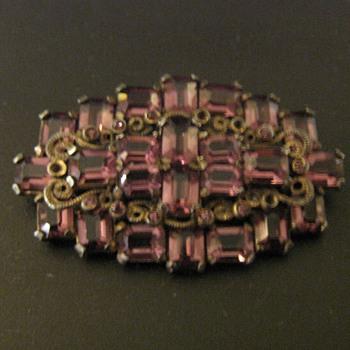 Faceted purple stones set in base metal