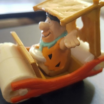 Fred Flintstone driving his car.