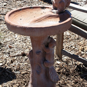 Two squirrels on a faux bois tile birdbath