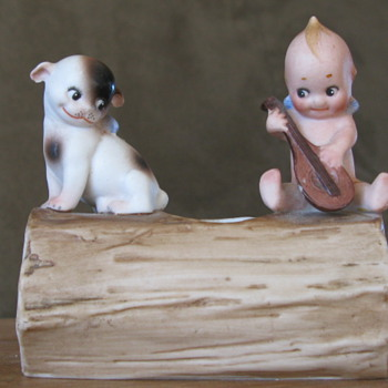 Kewpie playing a mandolin on a log with Doodle Dog - Figurines