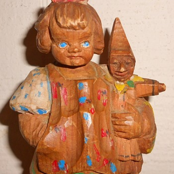 Wood carved doll holding elf doll