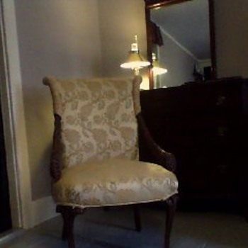 Upholstered chair with french provincial legs, and harvest motif carved arms.