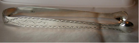 An early pair of flared, Adam style tongs by Benjamin Mountigue, dated c1780