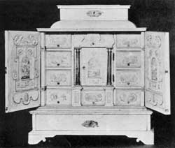 ILLUSTRATION VII: A 17th-Century Italian Cabinet:  Made of polished bone and decorated with miniature landscapes the door in the center, flanked by column pilasters, is the same design used in English and American desk interiors of the 18th and early 19th Centuries. When this central door is opened it discloses a compartment with a false back, behind which is a double tier of small drawers.