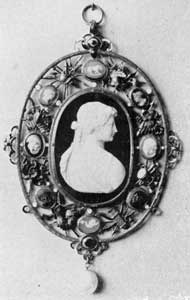 18th-Century English Pendant: The openwork frame for this cameo profile head is of gold set with smaller cameos, precious stones, and a large pearl finial. Such a piece of jewelry might have been imported, but it was probably too elaborate and expensive for the American taste
