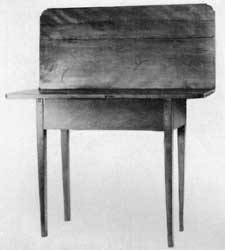 A Birch Card Table: Originally from central New Hampshire, it is an example of a village cabinetmaker's adaptation of the Hepplewhite style. Skirt and drawer front are of curly grained wood.