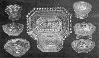 All Lacy Sandwich Pieces: In the center is an eight-sided deep dish, 7 inches long. Beneath it is a salt dish of the same shape. At the upper left is an octagonal salt dish with leaf design; and at the upper right, a circular one with round panels depicting the ship Cadmus.
