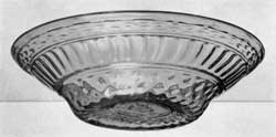 Illustration II: A Magnificent Blown-Three-Mold Bowl: Of brilliant clear green glass, light tone, this piece was probably blown at Kent, Ohio, in a decanter mold. The pattern consists of vertical ribbing between wide bands of diamond diapering. The band of gadrooning which encircles the shoulder in decanters has been almost entirely lost or obliterated in expansion of the bowl. Several of these bowls are known in light green glass and three or four in a glass of olive-yellow tone. This bowl is, so far as known, unique in size and widespread sides.