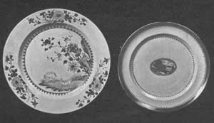 An Early and a Later Plate: At the left, a plate about 1760. The design in overglaze enamel shows a landscape with sheep, a European motif, with floral scrolls that are typically Chinese. The flowers in general are in pink and purple and the colors very clear. The glaze has a bluish tint. The plate on the right with small central medallion dates about 1820 and is typical of the later period of this ware. The medallion depicts an Occidental landscape. This and the narrow border are in a rust red with some gold.