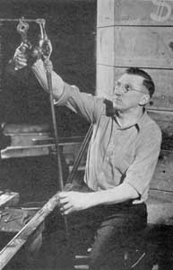 Applying the Stem: Here the gaffer, seated at his bench and using parrot shears, is steadying a gather of glass, as it is applied to the bulb with a pontil rod that will form the goblet stem.