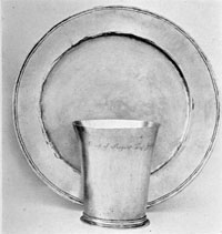 By Cesar Ghiselin: In their simplicity, this beaker and alms basin are typical of the 17th Century. Ghiselin was born in England, reached Philadelphia by 1693, and died in 1733, having worked for some years in Annapolis, Maryland.