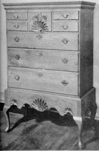 Cherry Chest on Frame: The flat cornice molding and sunburst carvings are characteristic of the earlier work of the Queen Anne period, particularly in New England.