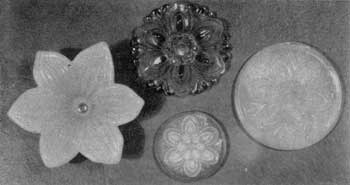 Four Sandwich Tieback Rosettes: Except for the one in the upper center, all are of opalescent glass. That at the lower left is a copy in glass of the clematis flower. The others are all of the same conventionalized floral design but show minor variations.