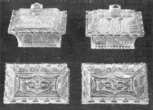 Illustration V - Covered Honey Dishes with Trays: These oblong covered dishes and trays, in Gothic pattern, are of like design except for the covers. One cover is curved, the other flat with two steps. Heart-bordered trays fit dishes although design differs. Trays are 7 inches long.