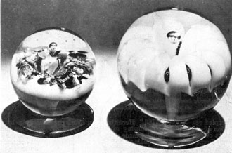 Two Millville Lily Paperweights: The footed example at the left, probably made by Marcus Kuntz, has a flower of turquoise blue with opal background. That at the right by John Rhulander is a lily formed of white glass with the stem very distinct, extending upward from the foot.