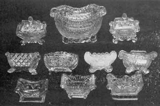 Elaborate Oblong Salt Dishes: In the center of the top row is a Lacy Sandwich sugar bowl that is 6 inches wide. On each side is a sofa-shaped salt dish with cover. Those in the next row show the variety of patterns used; while in the bottom row are two that follow the Napoleon bed in outline.