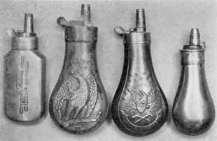 "Plate II – Four American Flasks: Right to left they are marked ""Robbins and Lawrence Co., Patent Revolving Hammer Pistol, Windsor, Vt.""; ""Colt's Patent"" used with 44 so universally popular with western adventurers; an army officer's flask hearing the motto, ""E Pluribus Unum""; and a smaller unmarked pistol flask with graduation to regulate the amount of the charge of powder."