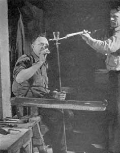 Ready for the Lehr: The goblet is now made and the gaffer is freeing it from the pontil rod as his servitor holds the fork by which the finished piece, still too hot to handle, will be taken to the annealing lehr for the gradual process of cooling. When cold the roughness where the pontil was once attached will be removed at a series of grinding and polishing wheels.