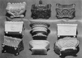 Salt Dishes in Opaque Glass: Some of these, notably the round-footed dish, second row center, and the oblong one, lower row left, were executed to simulate the earlier Wedgwood pottery with raised classic decorative motifs. The others are from molds used also for transparent and opalescent glass.
