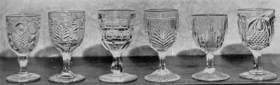 Six More Pattern Glass Goblets: The individual patters are, left to right: Horn of Plenty; Inverted Fern; and unidentified deisgn; Ribbed Palm, Icicle, and New England Pineapple.