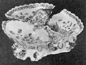Illustration II: Sweetmeat Dish: This example, made at the Bow factory about 1755, has a simple Chinese floral decoration. The modeling of the three compartments are somewhat shell-like in feeling.