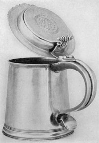 Illustration IV: Tankard by Peter Quintard: Although plainer in decoration, the form and proportions are practically identical with those of the tankard made jointly by LeRoux and Quintard. The latter's touch-mark can be seen on both pieces at left of handle just beneath the rim. The lid is decorated with circular engraved design.