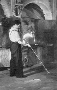 The Start, Blowing the Bulb: Standing before the furnace, a glass blower has expanded the gather of molten glass on his blow pipe. When finished this will be the upper part of the goblet.