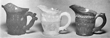 Three Sandwich Cream Pitchers: All are in shades of blue. The right is of streaked opaque glass. The design of that at the left is a combination of the acanthus leaf with diamond-cut shields; that of the one in the center, the Gothic pattern and peacock feather border; and that at the right, the Gothic pattern and the chain border.