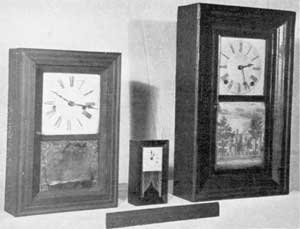 Three Variations in Size: Left to right, a miniature by Manross; center, a very small example made quite late by the New Haven Clock Co.; and right, a small size of the standard clock in ogee case made by J. C. Brown.