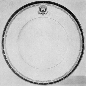 Designed by Franklin Delano Roosevelt: In this White House dinner service the outer border is under mat cobalt blue with gold stars. The motifs of the inner border are a rose and three feathers adapted from the Roosevelt coat-of-arms. The Presidential seal, also on the rim, is executed in colors.