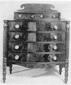 An Empire Chest of Drawers: Of mahogany with drawer fronts characteristically of crotch-grain veneer, this piece when in the Warren Cramer Collection was attributed to Joseph Cushing who worked in Boston about 1820.