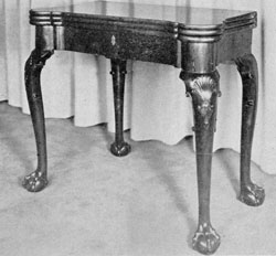 Georgian Gaming Table: Made of mahogany, circa 1740, it has four cabriole legs terminating in boldly carved ball-and-claw feet. The triple top, when opened, shows a backgammon board, places for candles, and wells for dice and gambling counters.