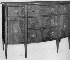A Hepplewhite Butler's Side Board: An example of Salem, Massachusetts, cabinetmaking. It was made about 1800-1810. The top drawer is fitted as a desk. When pulled out, the front folds down to make it practical for writing. It was made of crotch grain mahogany veneer with decorative inlays of wood of contrasting colors.