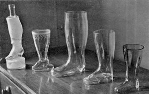 Illustration III: Boots and Shoes in Glass: The three at the right are boots in clear glass. The largest, center, is 10 1/4 inches high. The one at the extreme left, which is a bottle, has a frosted finish. Its base is a hassock. It has a total height of twelve inches.