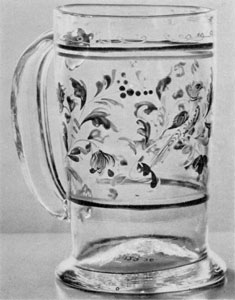 A Stiegel-Type Mug: Of clear glass, it is decorated with enamel in various colors, done in a leaf design, with bands top and bottom.